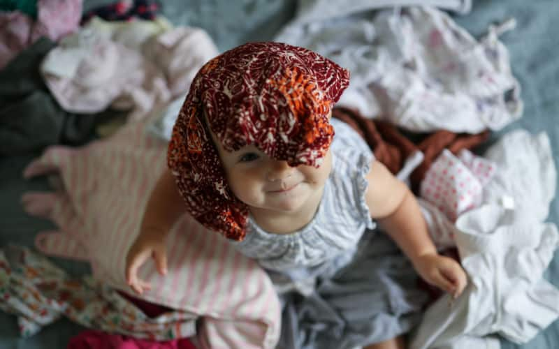 baby with clothes on her head as her mom shops for kids