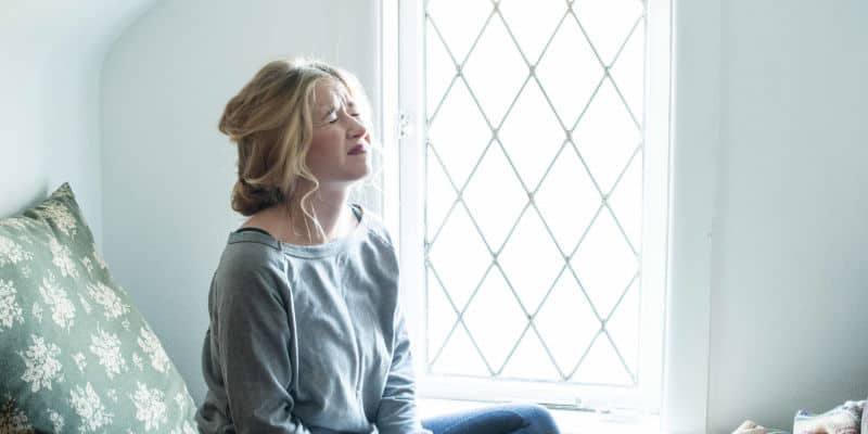 overwhelmed mom sitting by window wincing or crying