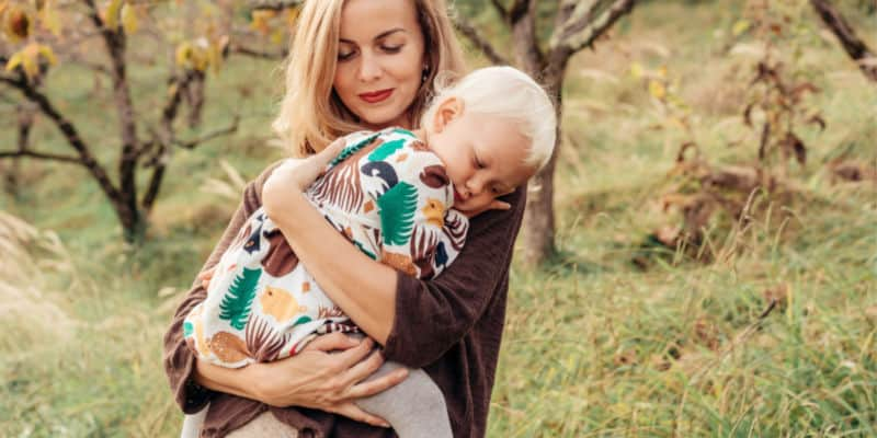 mother cuddling her child in a meadow