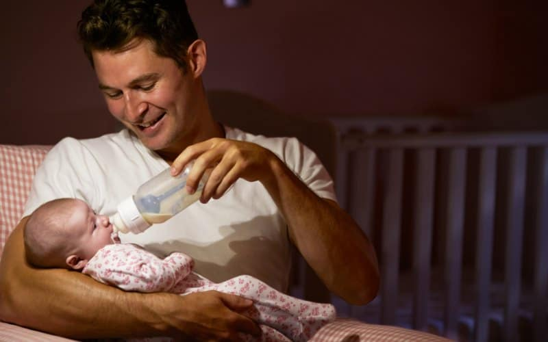 dad feeding baby daughter with a bottle