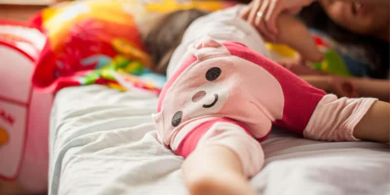 older baby sleeping on bed with pajamas on, irish twin