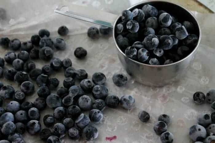Unstick the blueberries from the tray or wax paper, separate them into desired amounts, then freeze those blueberries in bags together.