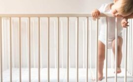 baby in white onesie climbing out of crib