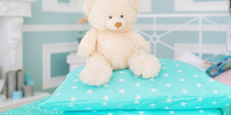 teddy bear sitting on top of a light aqua pillow with stars