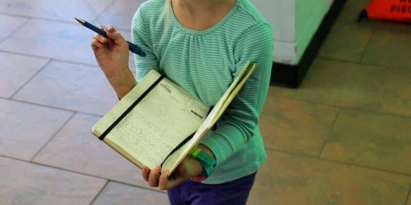 girl looking at a list in a notebook