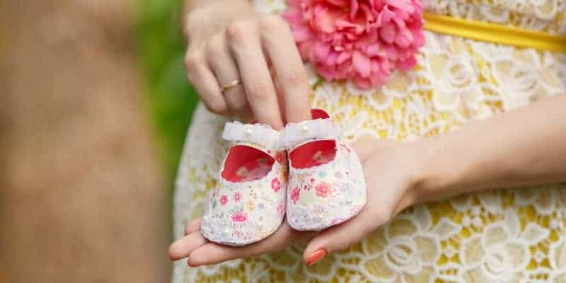 mom holding baby shoes