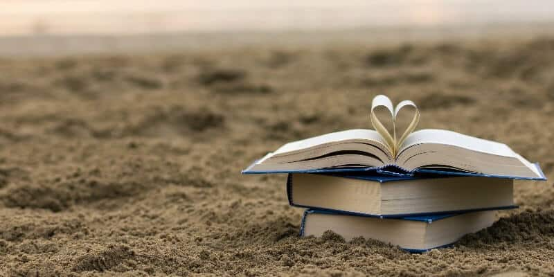 three books on the sand at  a beach