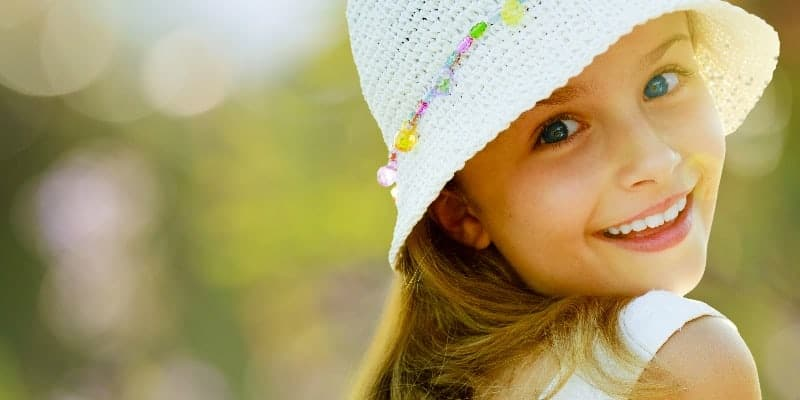 young girl with a hat smiling over her shoulder