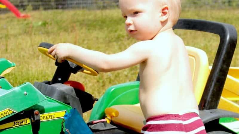 toddler climbing into toy car