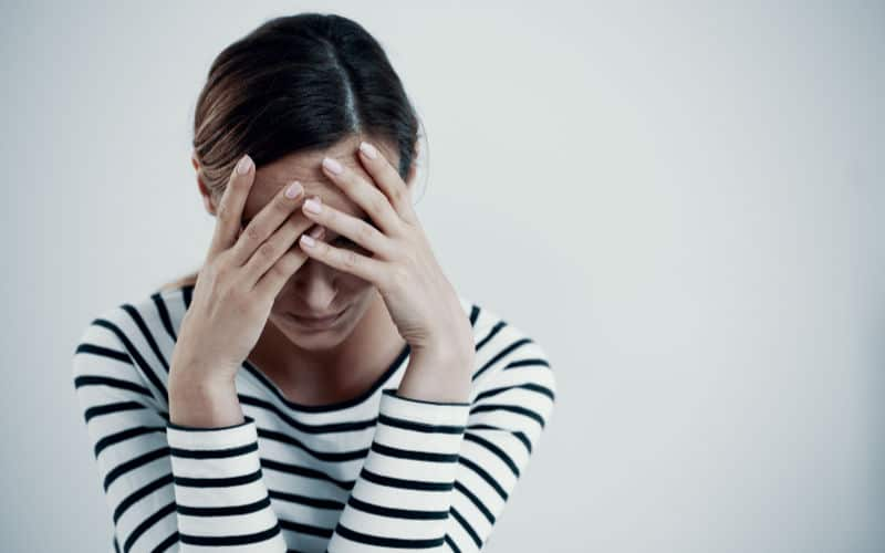 woman with white striped shirt with hands on face in survival mode