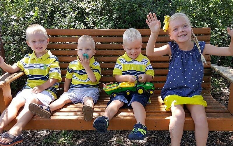 4 kids sitting on a swing
