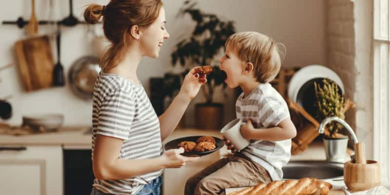 mother feeding her toddler breakfast in the morning