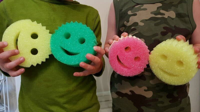 kids holding up cleaning sponges
