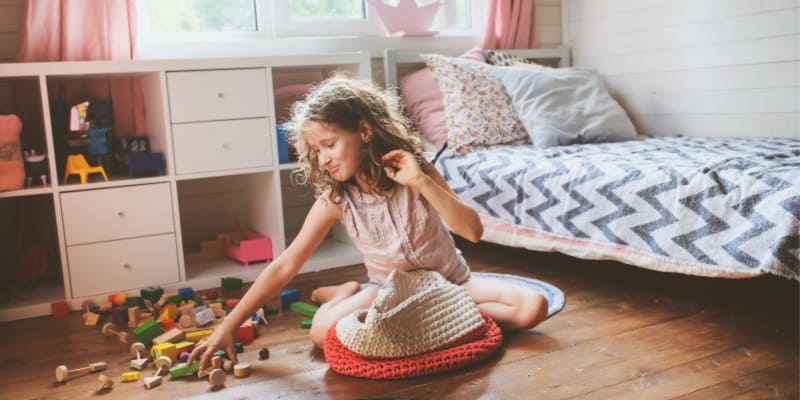 a girl cleaning up the toys in her room