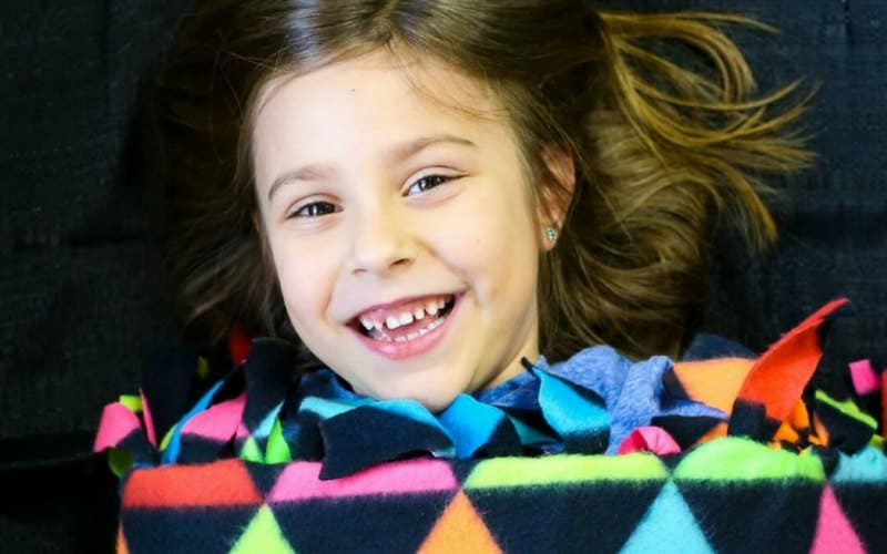 girl with blanket smiling
