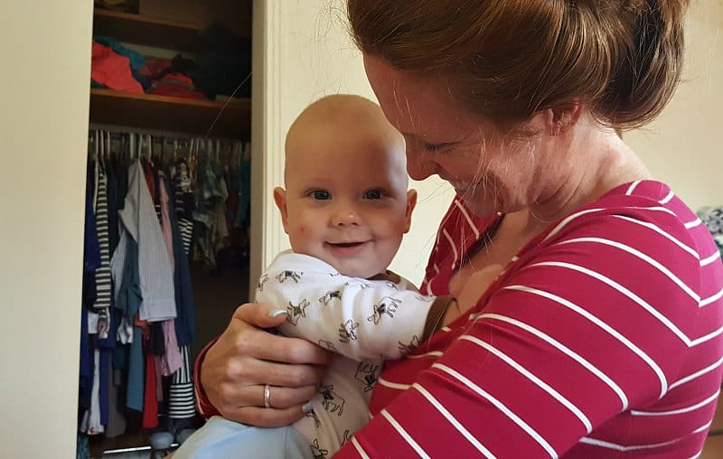 mom smiling at baby who is grinning at camera