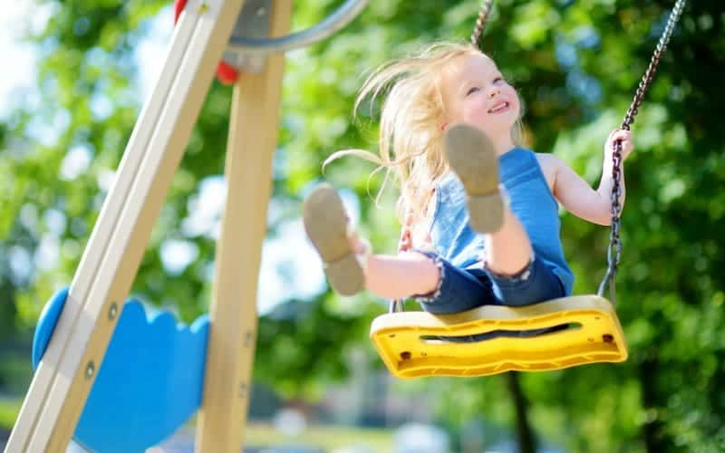 little girl swinging during independent play