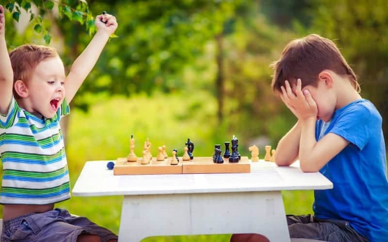 little kid rejoicing that he won chess while opponent is being a sore loser