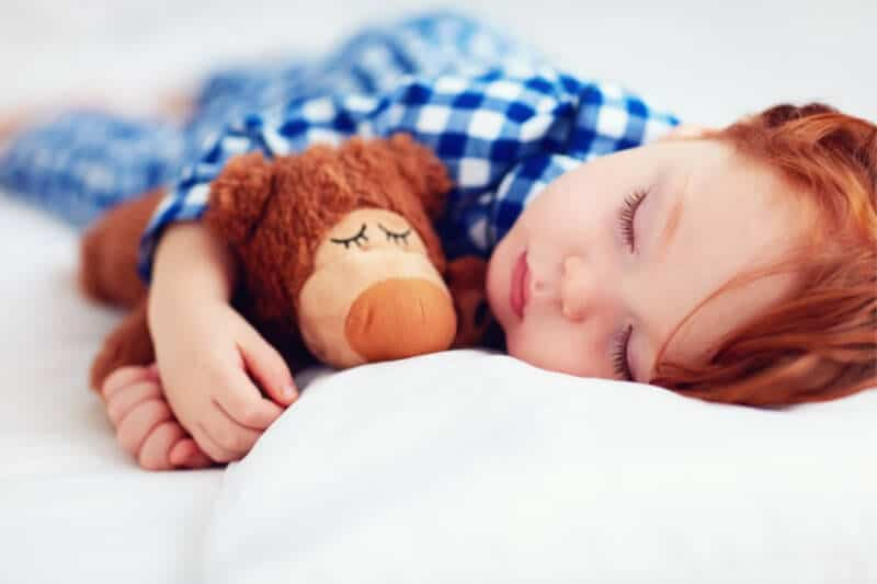 parenting toddlers and tips to help you stay sane. Redhead toddler sleeping in white bed.