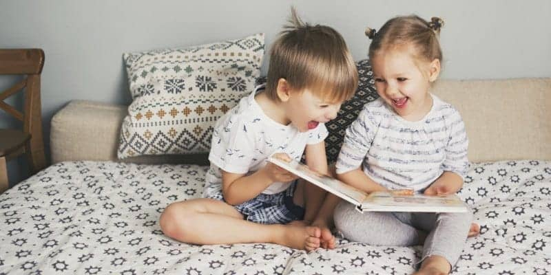 toddlers and preschoolers reading books on bed
