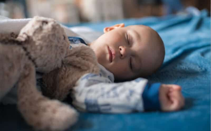 baby sleeping on bed with blue blanket and a teddy bear.