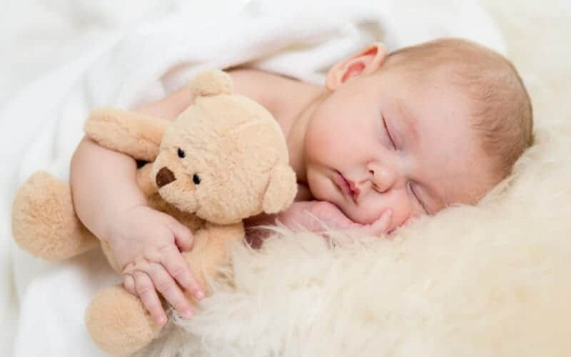 baby sleep lifesaving tips. Baby resting on soft bed with sheepskin and a teddy bear for baby sleep tips
