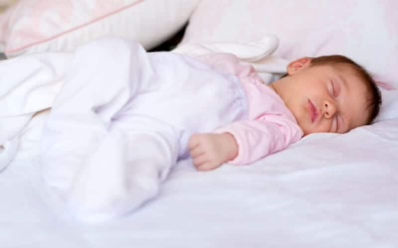 tips for baby sleep. Baby sleeping on white bed with pink onesie and white pajamas.