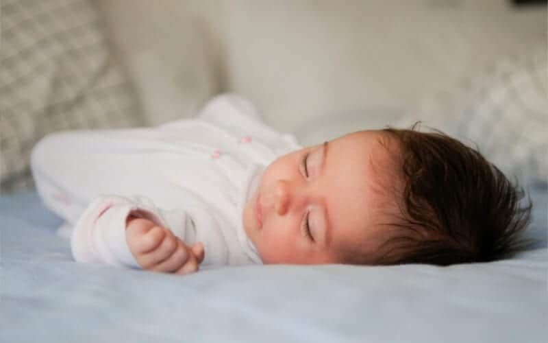 baby sleep tips for little babies and infants. Baby sleeping on bed with dark hair and light blue sheets and white onesie.