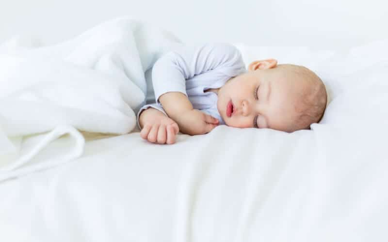 baby sleep tips and advice to help your little one sleep well. White bed with baby sleeping on it in light blue onesie.