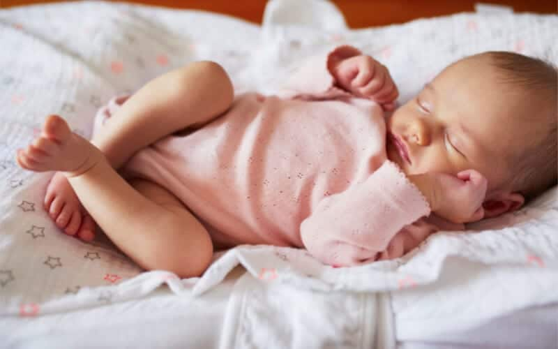 baby sleep advice and baby sleep tips and baby sleep help for infants. Baby sleeping on bed on a blanket with a pink onesie.