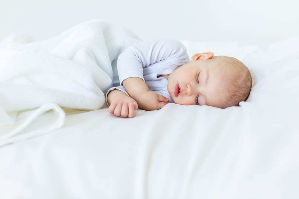 baby in blue onesie lying on bed. 3 month old baby sleep routine