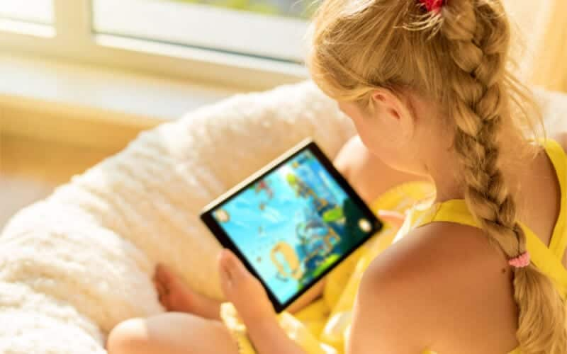 girl in yellow sitting on her bed and playing on an iPad