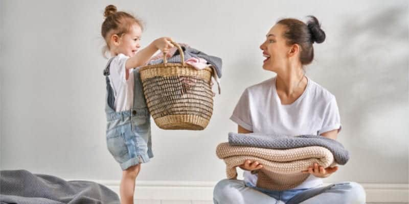 minimalist mom with daughter holding laundry basket