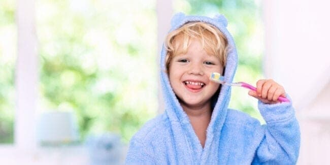 4 year old in blue robe brushing teeth