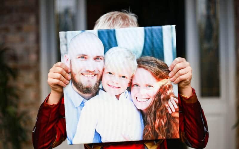 a child holding a sentimental christmas gift, a canvas of the family