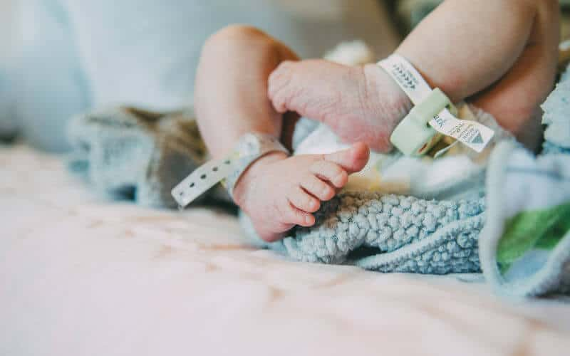a newborn baby's feet with the hospital bands still on