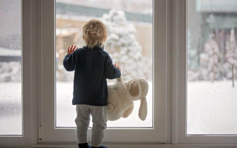 toddler standing by window focusing on the snow with his teddy bear