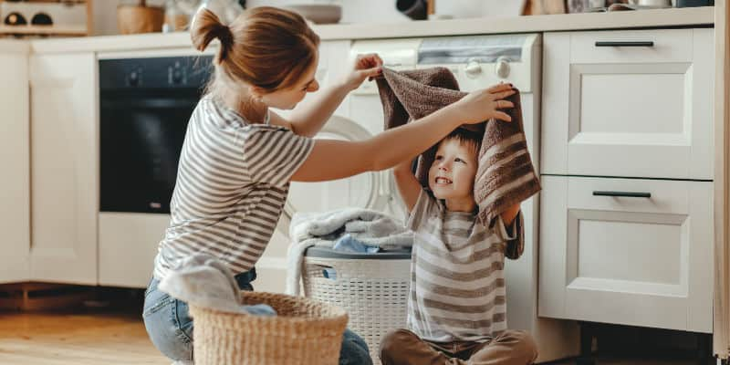 mother showing child how to fold clothes and do laundry