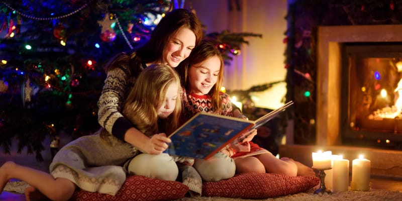 mother reading christmas book to children