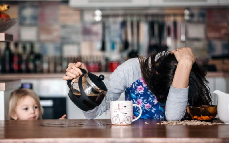 toddler looking at mom pouring coffee as part of her morning routine
