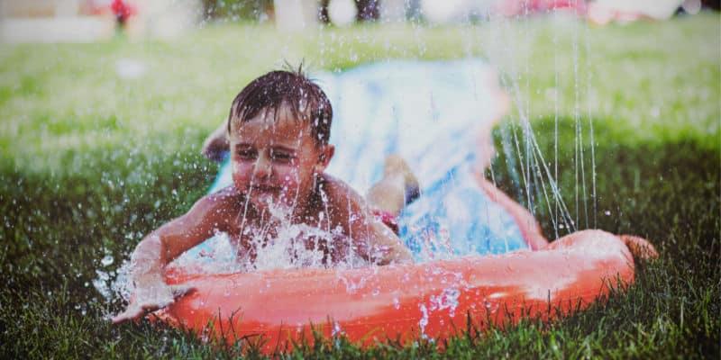 toddler on the slip n slide outdoors