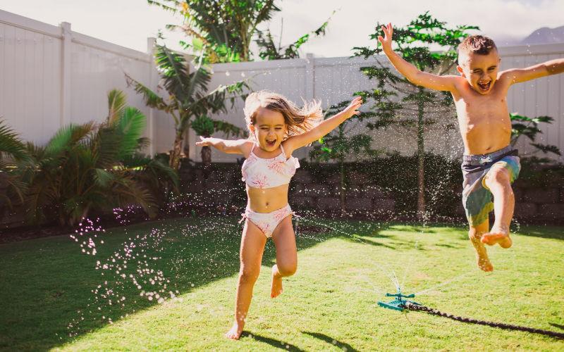 toddler and preschooler playing games in the sprinklers in their yard