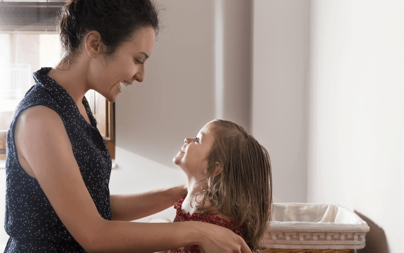 Mom is brushing girls hair as part of family routines.