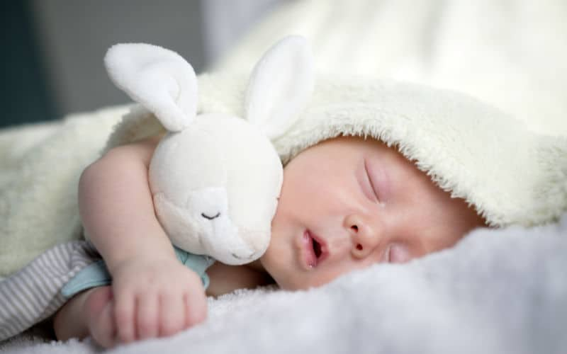 baby sleeping with blanket nearly over face not safe sleep